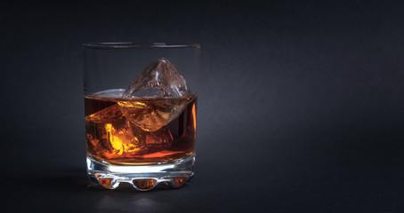 Whiskey with ice cubes on dark background