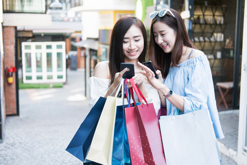 two young happy asian women shopping outdoor shopping mall in a