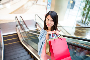 Woman holding lots of shopping bag and standing on escalator