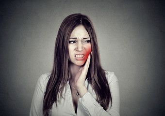 woman with sensitive toothache suffering from pain touching outside mouth .