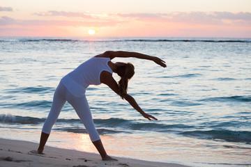 femme qui fait  de la gymnastique sur la plage au coucher du soleil