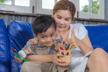 happy Asian family sitting on sofa comprising mother and son,Asian family concept