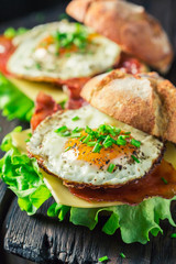 Closeup of homemade burger with bacon, eggs and cheese