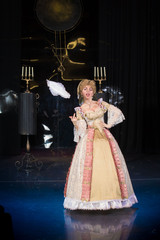 actress woman in a medieval dress with a puffed skirt is posing against the backdrop of the scenery for the play