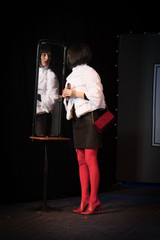 actress brunette woman in a sexual way against the background of a theater stage with scenery for the play.