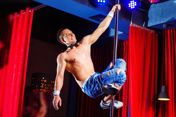 Male pole dancer is hanging at pole in striptease bar.