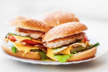 Closeup fresh homemade cheeseburgers on white plate isolated.