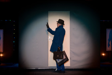 Male actor in a blue suit plays a role in the background of a theater stage with scenery for the play.