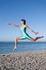 femme qui saute en dansant sur la plage