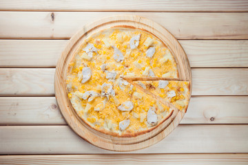 Pizza with pineapple on the wooden background