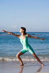 femme qui fait des exercices de gymnastique sur la plage en été