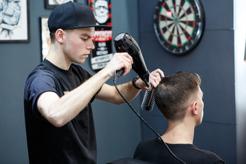Master cuts hair of men in the barbershop, hairdresser makes hairstyle for a young man