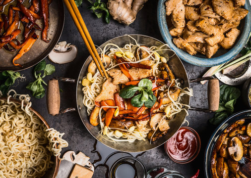Asian kitchen table with food bowls, wok , stir fry , chopsticks and ingredients on background, top view