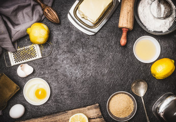 Top view of bake preparation with kitchen tools and ingredients for cake or cookies : lemon , flour, egg, raw sugar and butter on dark rustic kitchen table background, top view, frame