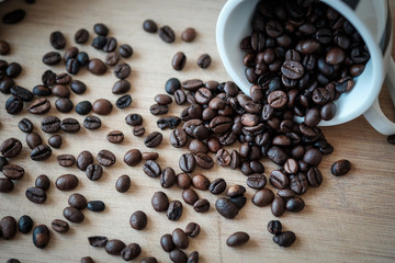 Detail view of coffee beans on wooden background. Macro shoot.