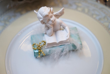 Close up photo of Festive table decoration with white plaster angel on plate.
