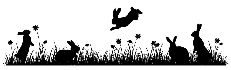 Silhouettes of Easter bunnies on a flower meadow