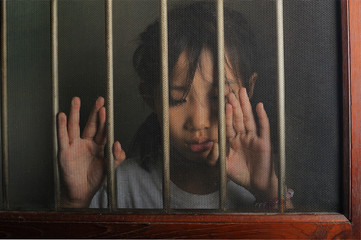 sad asian child standing behind the wire screen window.  Unhappy