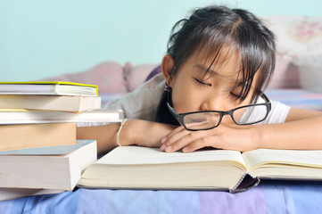 asian child sleeping while reading in the bed, selective focus
