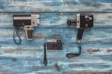 Video and photo camera on a blue old vintage blue background. Photographed in retro style