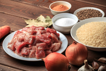 Cooking ingredients. Sliced raw meat, rice, spices, garlic, carrot, onion, bay