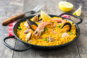 Traditional spanish seafood paella on wooden background