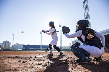 Female batter hitting the ball during a baseball game
