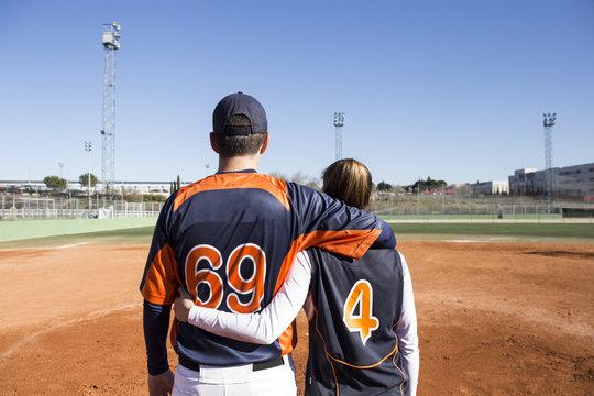 Rear view of baseball players embracing on a baseball field