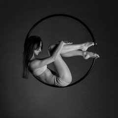 Young beautiful slim dancer on aerial hoop posing on a black studio background