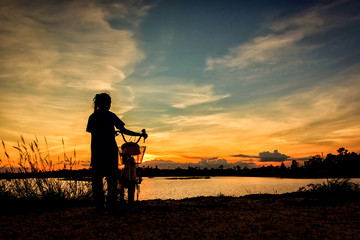 Asian girl and her bicycle at sunset on lake.