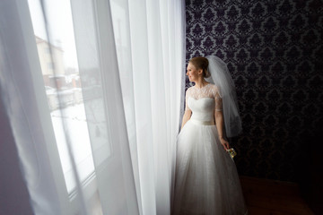 nice and gentle bride in a white dress standing at home