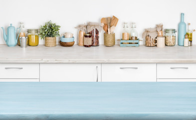 Blue empty wooden kitchen table over blurred food ingredients background