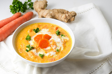 Carrot soup with ginger root and parsley garnish, white napkin