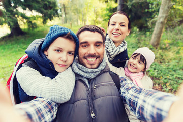 family with backpacks taking selfie and hiking