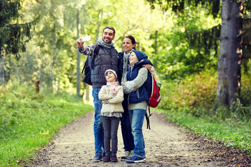family taking selfie with smartphone in woods