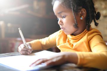 Little African girl writing.
