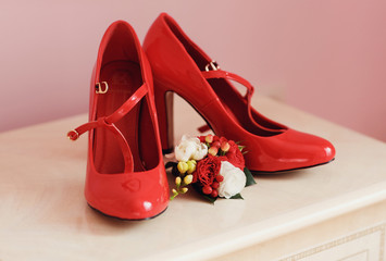 Red bridal shoes and wedding boutonniere