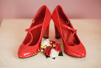 Bridal shoes and boutonniere with the red flowers