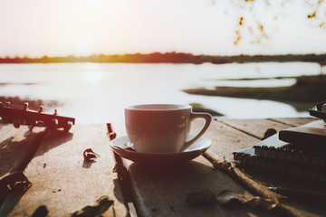 coffee on wooden floor with lake view background at sunset time.