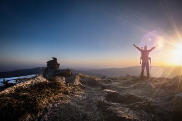 Alpiniste face au soleil levant