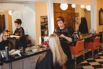Female hairdresser styling clients hair in salon