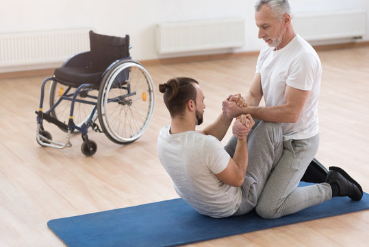 Skilled orthopedist assisting the disabled in the gym