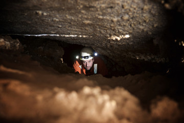 High angle view of spelunker standing in cave