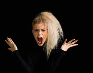 Angry blonde girl portrait screaming on black background