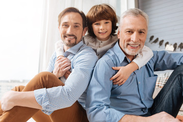 Nice delighted boy hugging his family