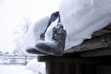 Low section of woman wearing rubber boots sitting on snow covered wood