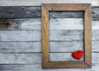 Red heart in wooden frame with space on old wooden floor background
