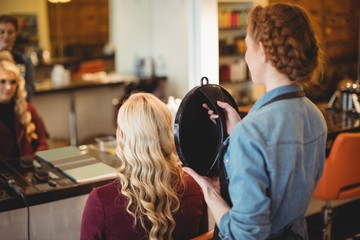 Female hairdresser showing the haircut of client in mirror