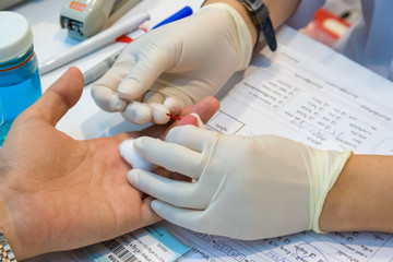 A nurse takes blood from a finger on the analysis