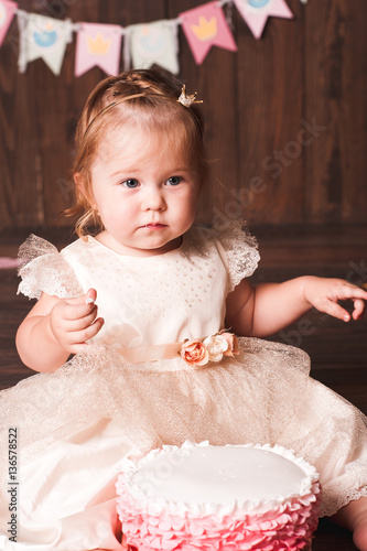 Cute baby girl 1 year old wearing stylish dress sitting with